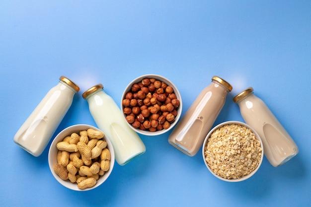 Бутылки веганского немолочного молока с различными орехами на синем