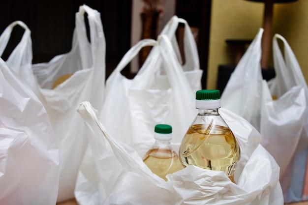 Бутылки с растительным маслом и много пакетов на полу, курьер принес домой тяжелые пакеты с продуктами, покупая продукты для доставки на дом из супермаркета.