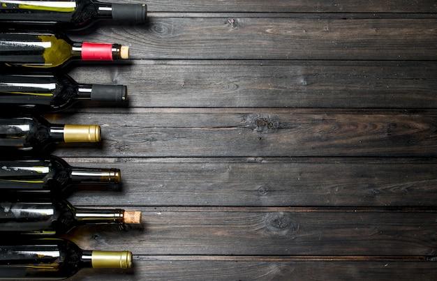 白と赤ワインのボトル。木製のテーブルの上。
