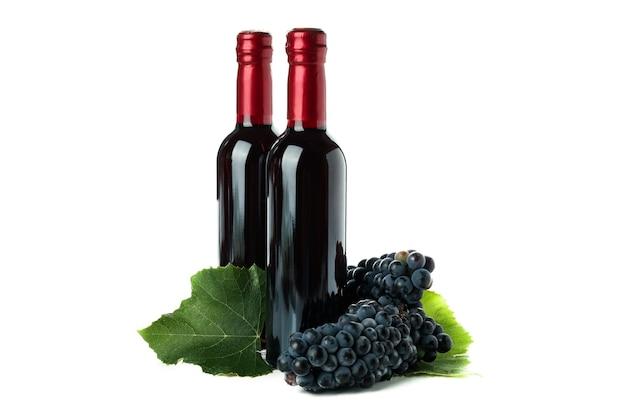 白い背景で隔離のワインとブドウのボトル