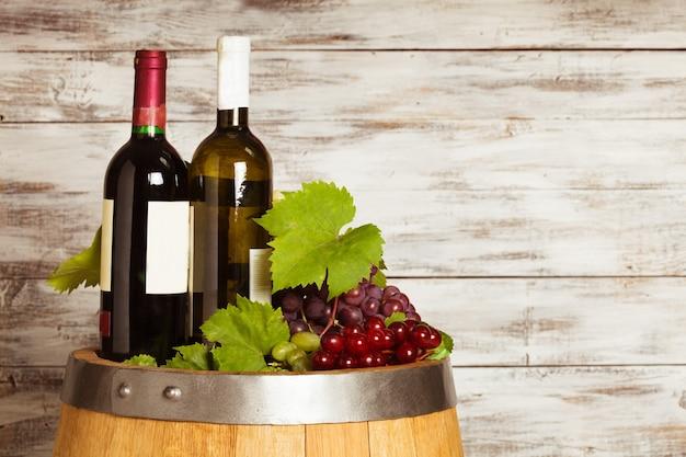 古いぼろぼろの木製の背景の上のオーク樽のワインのボトル
