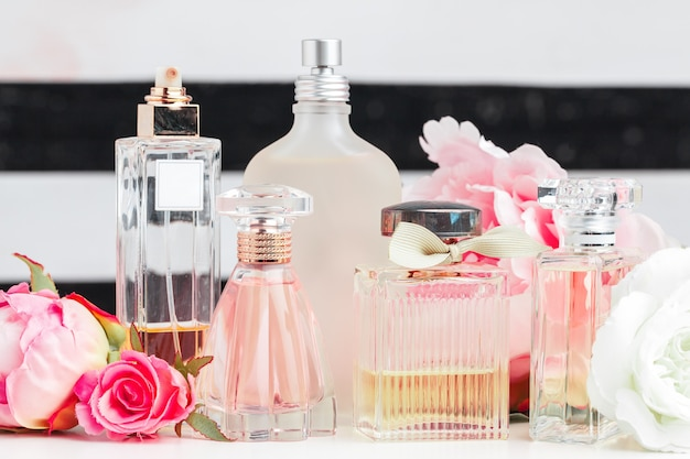Bottles of perfume with flowers on light