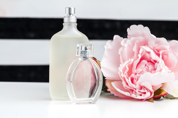 Bottles of perfume with flowers on white