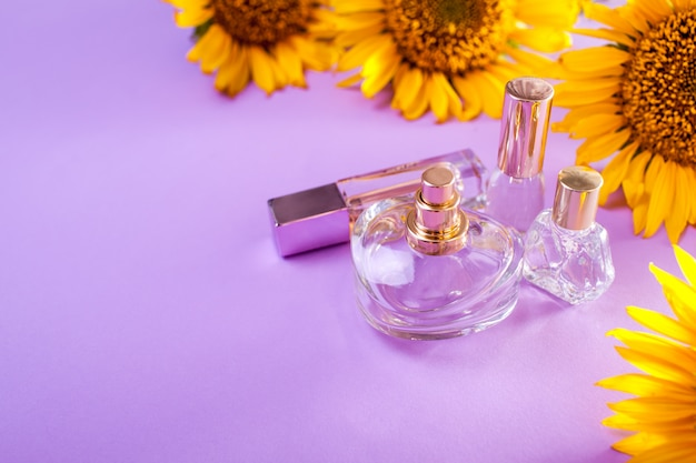 Bottles of perfume with sunflowers on purple. organic cosmetics
