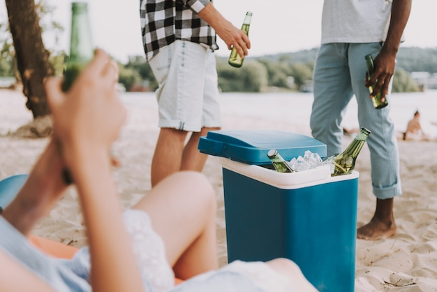 Bottles in portable refrigerator at beach party