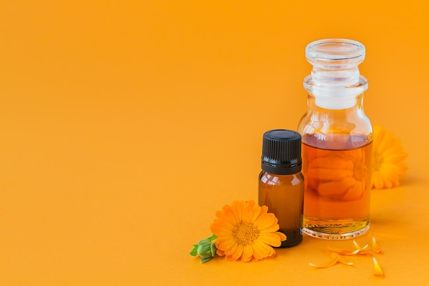 Bottles of pot marigold tincture or infusion and essential oil with fresh calendula flowers on an orange. natural herbal alternative medicine, healing and medicinal herbs.