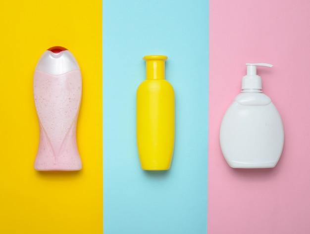 マルチカラーのパステル調の背景にシャワーとバスルームのボトル製品。シャンプー、液体石鹸、シャワージェル。上面図。平干し。ミニマリズムの傾向。