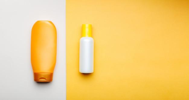 色付きの背景にシャワー浴室シャンプーヘアコンディショナーのボトル製品。スパトリートメントのためのヘアスキンケア製品。コピースペースを持つ長いwebバナー。