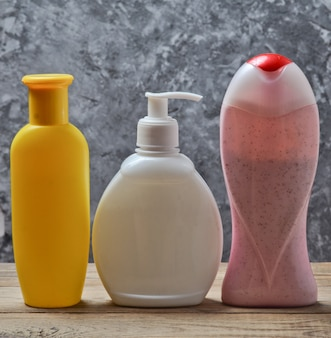 Bottles of products for a shower on a wooden shelf against a gray concrete wall. shower gel, shampoo, liquid soap.