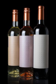 Bottles of red, white and rose wine isolated on black wall.