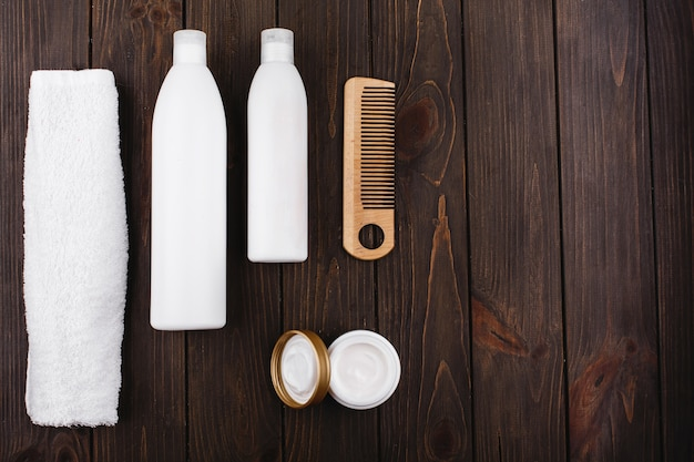 Bottles of shampoo and conditioner lie with towel and comb on wooden table