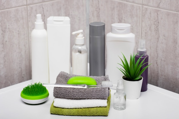 Bottles of soap and shampoo and cotton towels with green plant on a white table against the background of a bathroom