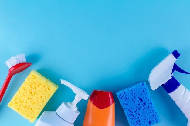 Bottles, sprays for cleaning the house, colored sponges for washing dishes and a brush