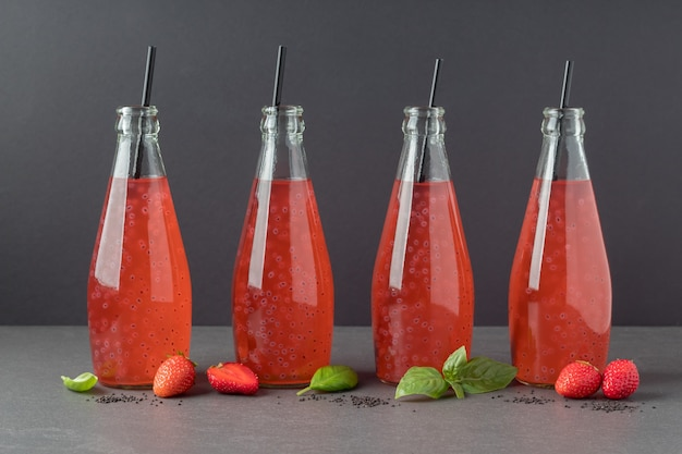 Bottles of strawberry drink with basil seeds on grey table trendy beverage for weight loss