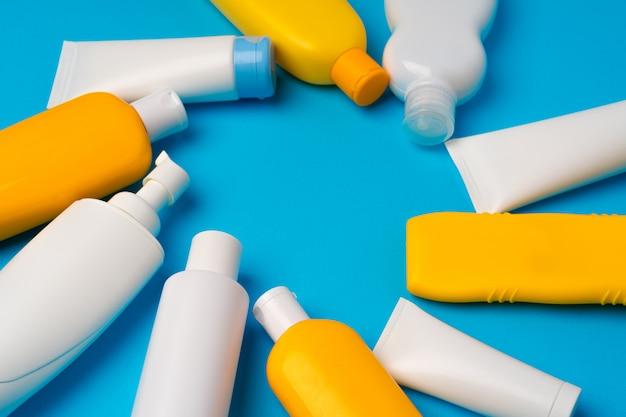 Bottles of sunscreen cream on blue background