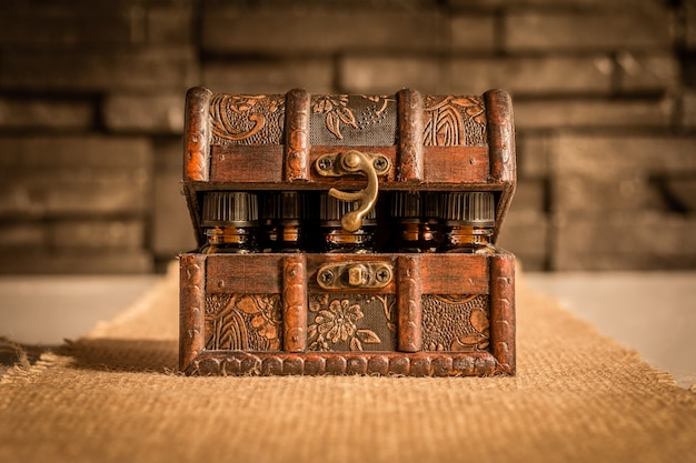 Bottles of tincture or potion in a retro styled.old treasure chest on fabric background