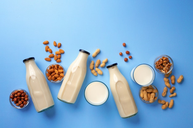 Bottles of vegan non dairy milk with various nuts on blue background, top view