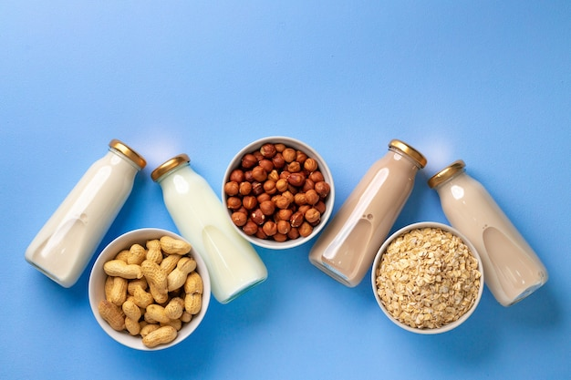Bottles of vegan non-dairy milk with various nuts on blue