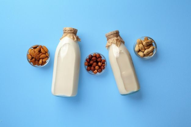Bottles of vegan non dairy milk with various nuts on blue