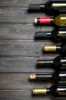 Bottles of white and red wine. on a wooden background.