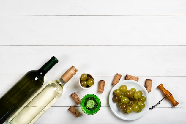 Bottles of white wine next to corks and grapes