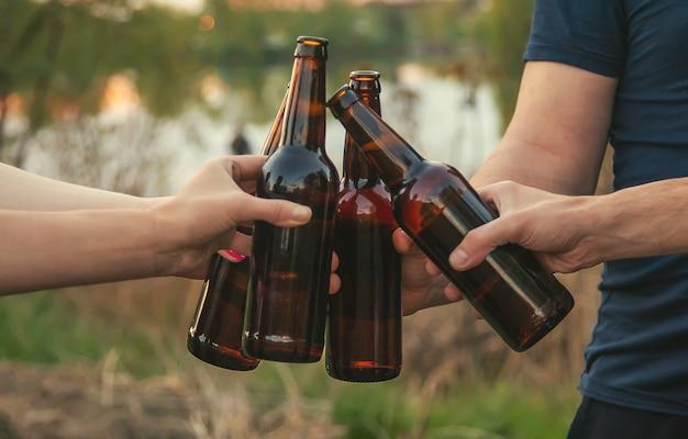 自然界の若者の手にビールが入ったボトル