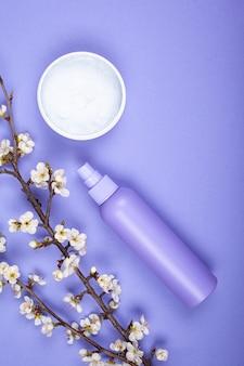 Бутылки с косметикой ухода за телом с белыми цветами на фиолетовом фоне вид сверху.