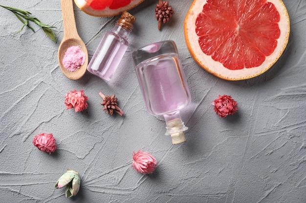 Бутылки с эфирным маслом цитрусовых и нарезанными фруктами на сером