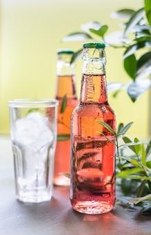 Бутылки с холодным розовым лимонадом и стакан с ледяным летним освежающим напитком