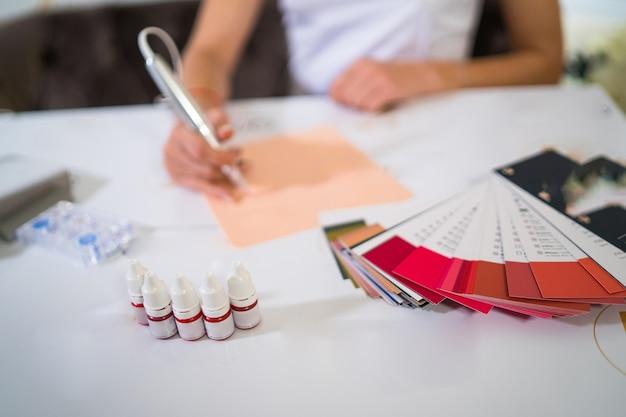 영구적인 문신을 위한 다채로운 빨간색 잉크가 있는 병. 전문 영구 문신 교육 자료. 확대.