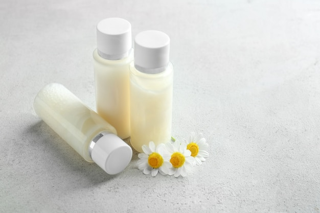 Bottles with cream and chamomile flowers on table