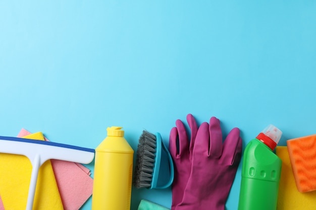 Bottles with detergent and cleaning supplies on blue background, space for text