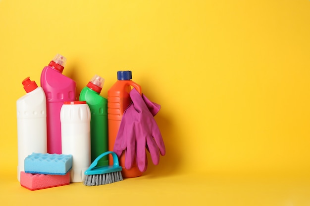 Bottles with detergent and cleaning supplies on yellow background, space for text