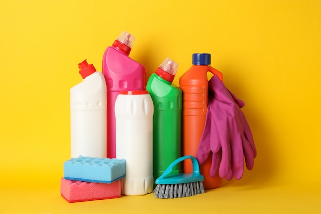 Bottles with detergent and cleaning supplies on yellow, space for text