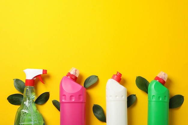 Bottles with detergent and leaves on yellow background, space for text
