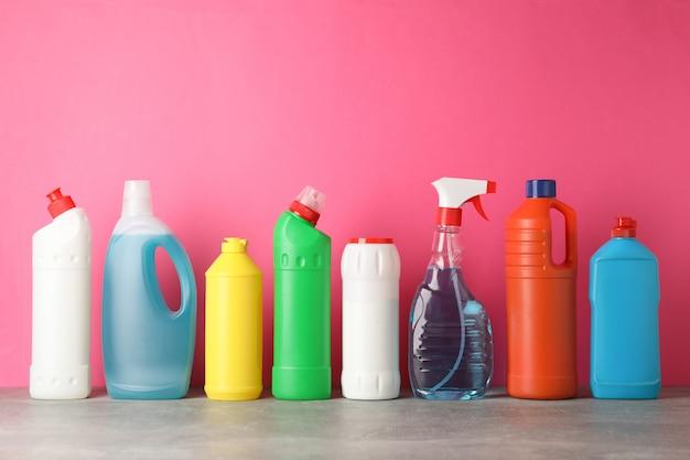 Бутылки с моющим средством на розовом фоне, место для текста