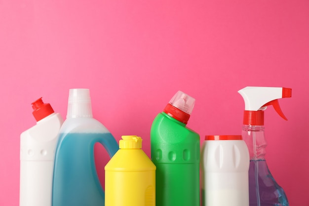 Bottles with detergent on pink background, space for text