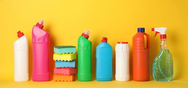 Bottles with detergent and sponges on yellow