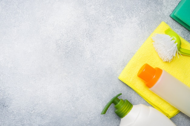 Bottles with detergents, brushes and sponges on concrete background.