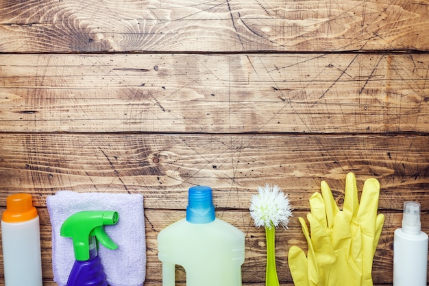 Bottles with detergents, brushes and sponges on wooden background.