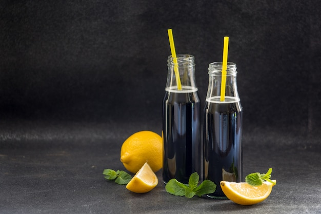 Bottles with detox activated charcoal black lemonade on table