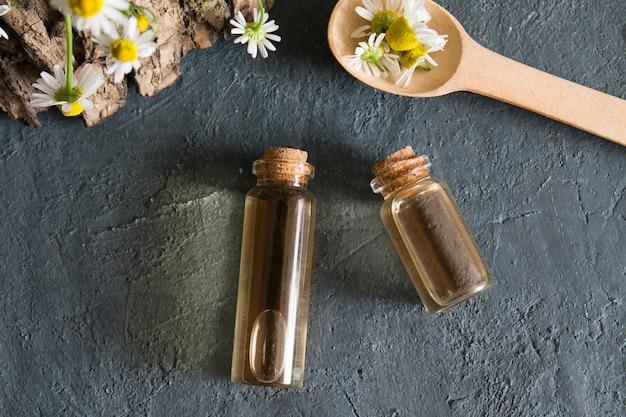 Бутылки с эссенцией и ромашкой плоско лежат на темной поверхности