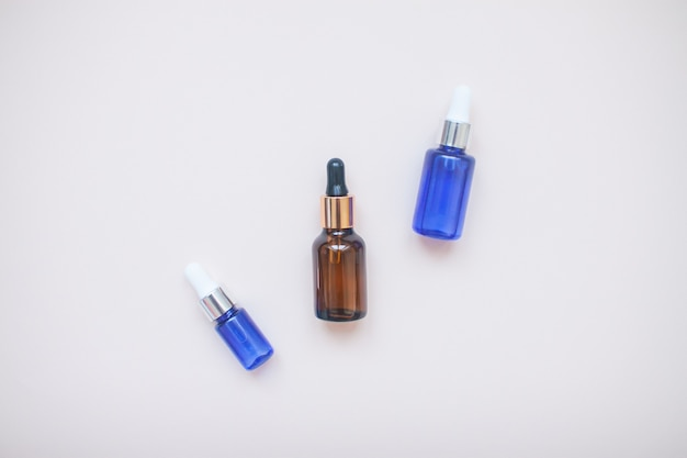 Bottles with face serum on gray. flat lay