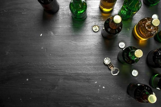 Бутылки со свежим пивом. на черной доске.