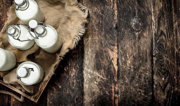 箱に入った新鮮な牛乳のボトル。木製の背景に。