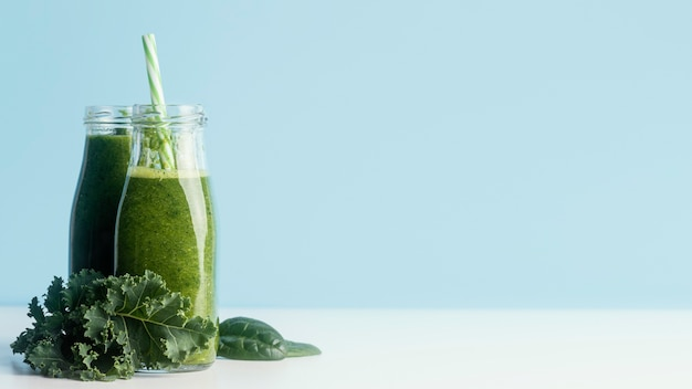 Bottles with green smoothie and copy space