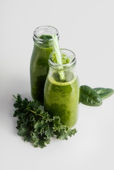 Bottles with green smoothie high angle