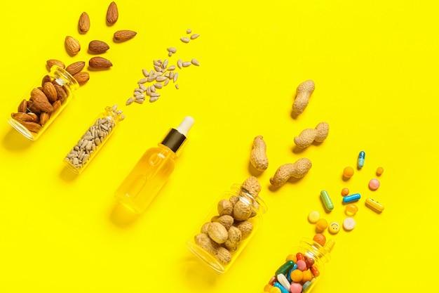 색상 표면에 건강한 견과류, 씨앗, 알약 및 기름 병