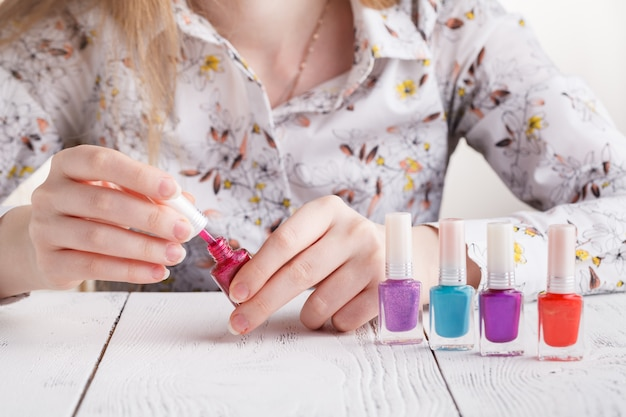 Bottles with nail polish in female hands