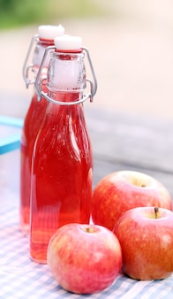 Bottles with red drinks and some apples
